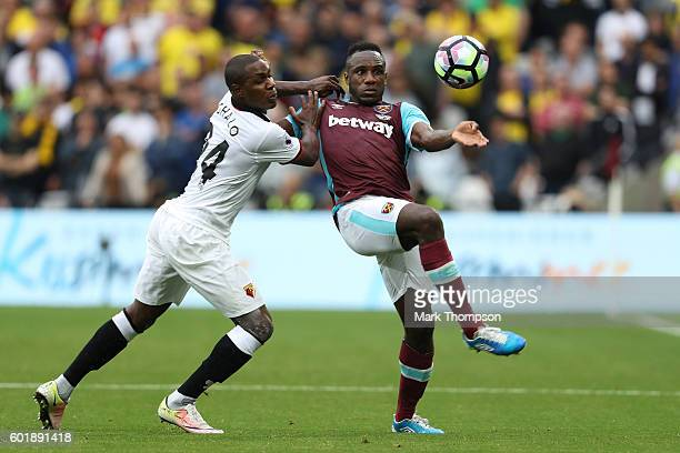 Odion Ighalo of Watford and Michail Antonio of West Ham United battle for possession during the Premier League match between West Ham United and...