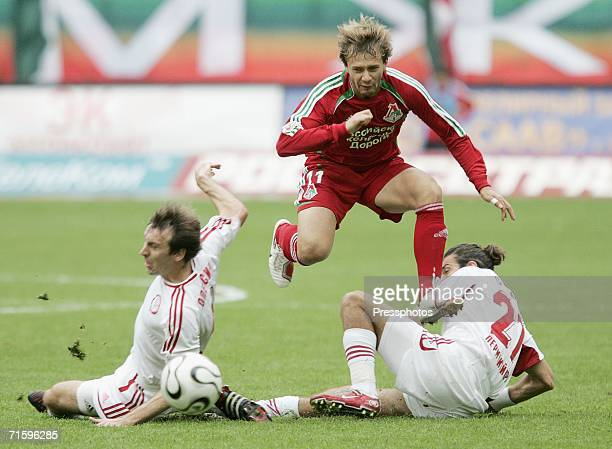 ODmitri Sychev of Lokomotiv Moscow competes for the ball with Ghenadie Olexici and Albert Sarkisyan of Amkar of Perm during a Russian League...