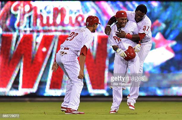 Odubel Herrera and Aaron Altherr of the Philadelphia Phillies congratulate Maikel Franco on his walk off single in the 12th inning against the San...