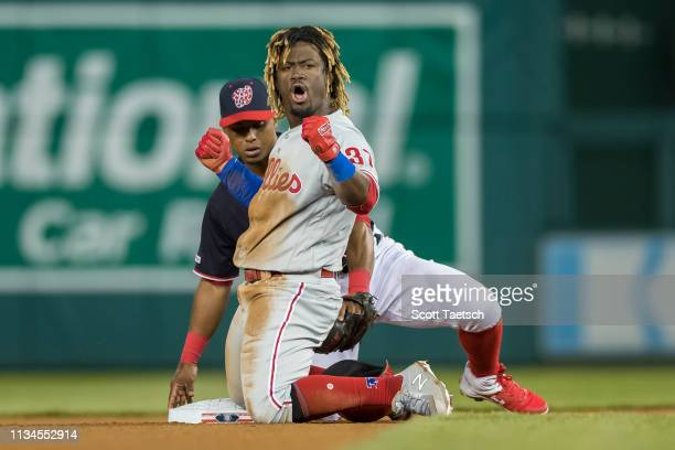 Odubel Herrera of the Philadelphia Phillies celebrates after sliding safely into second base in front of Wilmer Difo of the Washington Nationals...