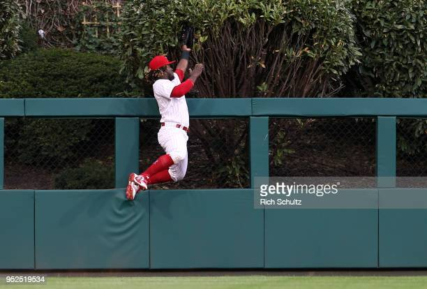 Odubel Herrera of the Philadelphia Phillies climbs the wall and makes a catch on a ball hit by Freddie Freeman of the Atlanta Braves during the third...