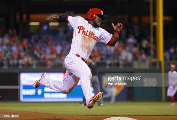 Odubel Herrera of the Philadelphia Phillies rounds third base and heads home in the ninth inning during a game against the St Louis Cardinals at...