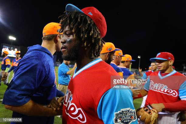 Odubel Herrera of the Philadelphia Phillies shakes hands with members of the New York Mets after the 2018 Little League Classic at Historic Bowman...