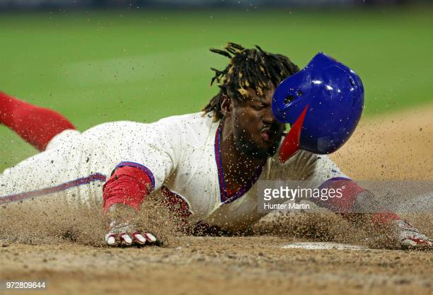 Odubel Herrera of the Philadelphia Phillies slides safely into home plate in the eighth inning during a game against the Colorado Rockies at Citizens...