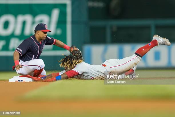 Odubel Herrera of the Philadelphia Phillies slides safely into second base ahead of the throw to Wilmer Difo of the Washington Nationals during the...
