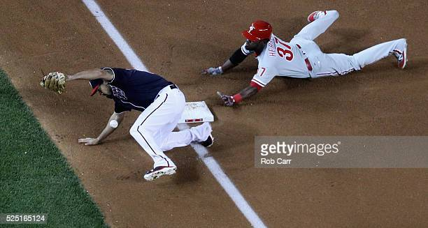 Odubel Herrera of the Philadelphia Phillies slides safely into third on a passed ball as Anthony Rendon of the Washington Nationals bobbles the ball...