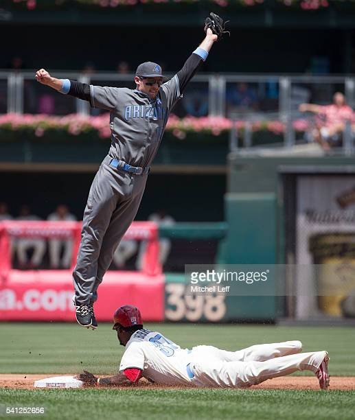 Odubel Herrera of the Philadelphia Phillies steals second base past a leaping Phil Gosselin of the Arizona Diamondbacks in the bottom of the first...