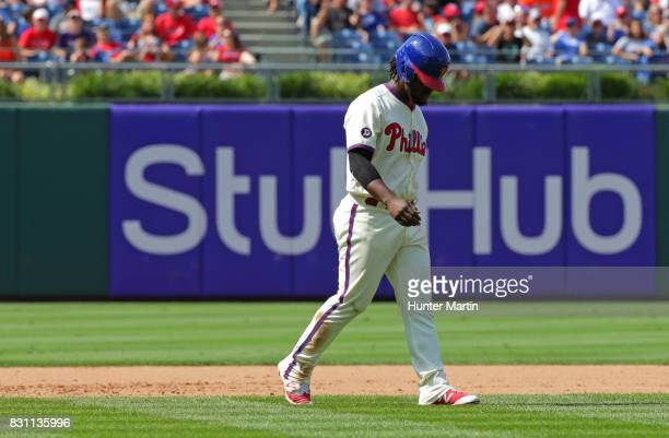 Odubel Herrera of the Philadelphia Phillies walks off the field after being called out at third base after trying to tag up from second base on a fly...