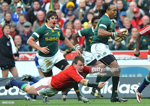 Odwa Ndungane of South Africa is tackled by Matthew Rees of the British and Irish Lions as a bloodied Jaque Fourie follows during their third test...