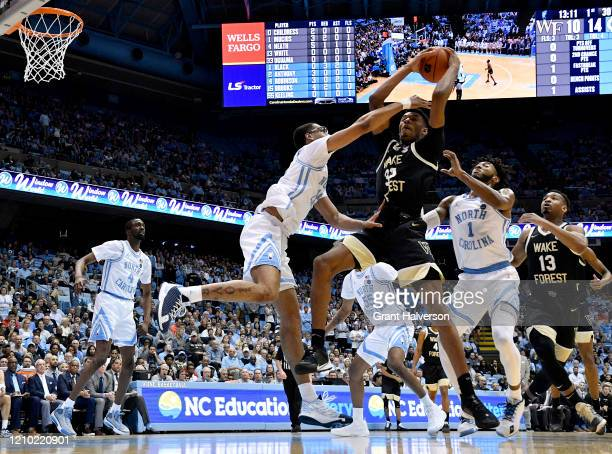 Ody Oguama of the Wake Forest Demon Deacons battles Garrison Brooks Leaky Black of the North Carolina Tar Heels for a rebound during the first half...