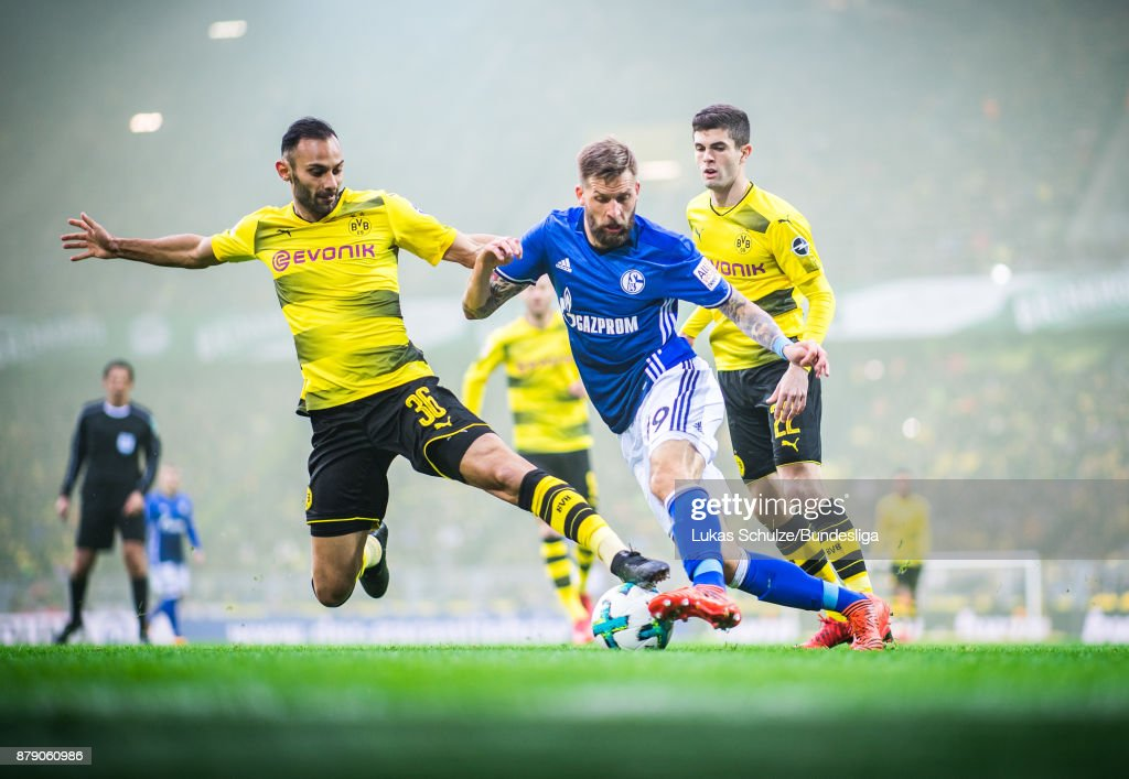 Oemer Toprak (L) of Dortmund and Christian Pulisic (R) attack Guido Burgstaller (C) of Schalke during the Bundesliga match between Borussia Dortmund and FC Schalke 04 at Signal Iduna Park on November 25, 2017 in Dortmund, Germany.