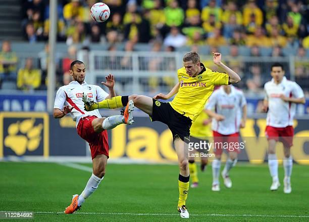 Oemer Toprak of Freiburg challenges Sven Bender of Dortmund during the Bundesliga match between Borussia Dortmund and SC Freiburg at Signal Iduna...