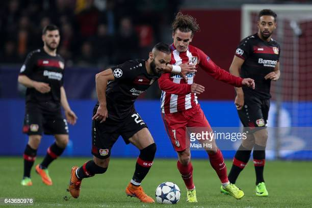 Oemer Toprak of Leverkusen is challenged by Antoine Griezmann of Atletico during the UEFA Champions League Round of 16 first leg match between Bayer...