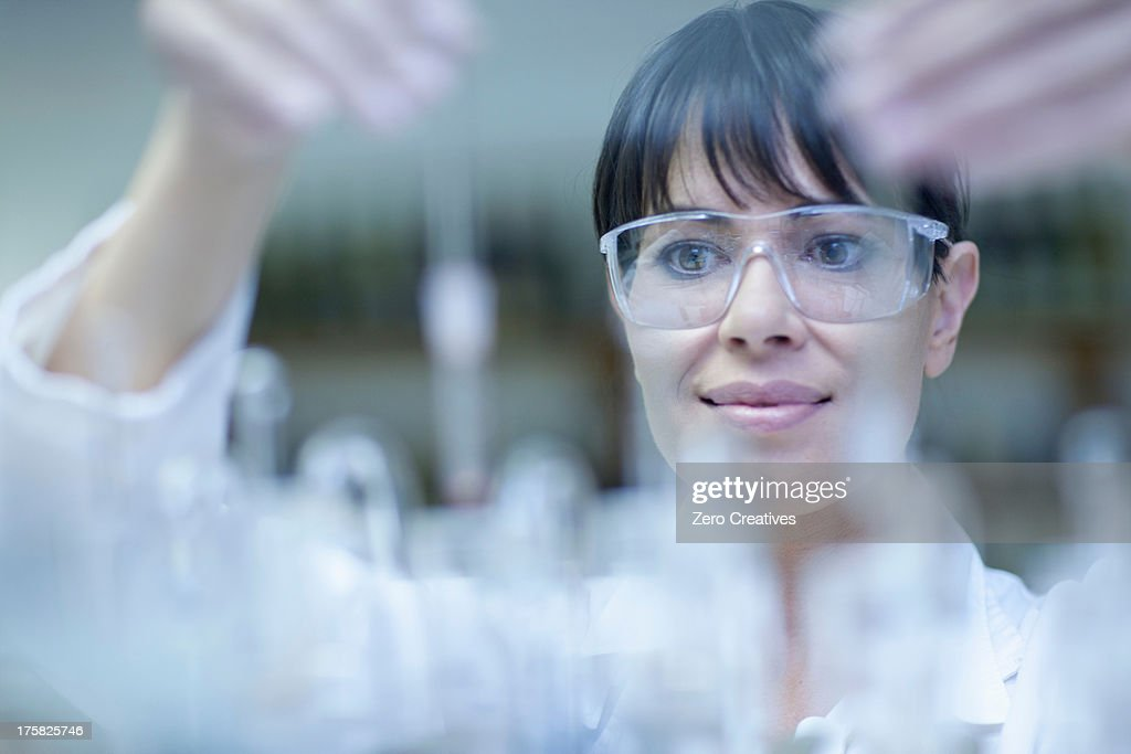Oenologist mixing during sample testing in laboratory : Stock Photo