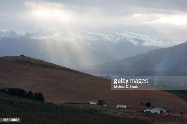oewerzicht farm in the foreground with the village of greyton in the distance, snow on mountains with sunlight piercing the clouds, overberg, western cape - overberg stock pictures, royalty-free photos & images