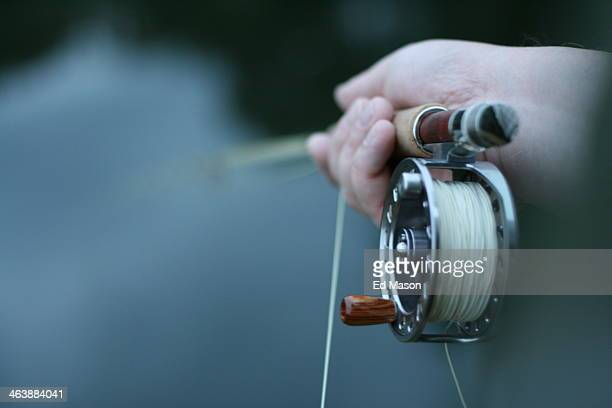 CONTENT] DOF of a hand holding a fly fishing rod