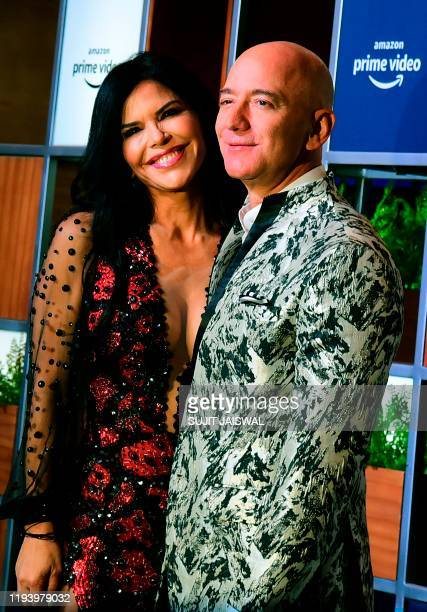 CEO of Amazon Jeff Bezos and his girlfriend Lauren Sanchez pose for pictures as they arrive to attend an event in Mumbai on January 16 2020