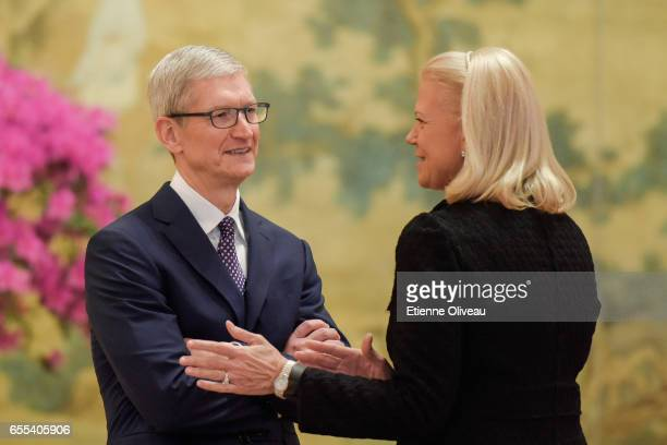 CEO of Apple Inc Tim Cook talks with Chairwoman President and CEO of IBM Ginni Rometty before the meeting with Chinese Premier Li Keqiang during...