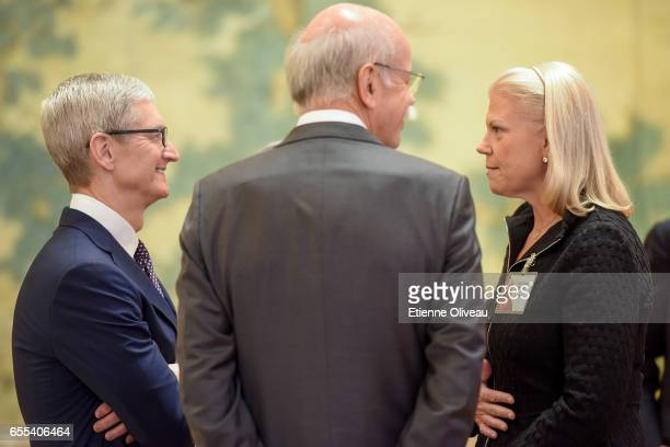 CEO of Apple Inc Tim Cook talks with Chairwoman President and CEO of IBM Ginni Rometty and CEO of Daimler AG Dieter Zetsche before the meeting with...
