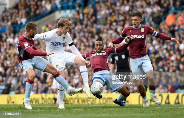 of Aston Villa tackles Patrick Bamford of Leeds United battles for the ball with Conor Hourihane Jonathan Kodjia and Jack Grealish during the Sky Bet...