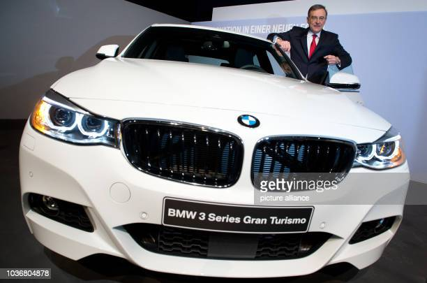 CEO of BMW Group Norbert Reithofer poses for the camera with a BMW 3 Gran Turismo at a press briefing on annual results of the automobile...