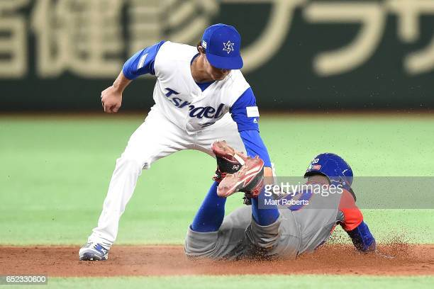 of Cuba caught stealing 2nd base and gets tagged out by Tyler Krieger of Israel in the fifth inning during the World Baseball Classic Pool E Game One...