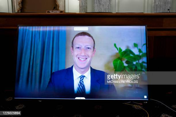 Of Facebook Mark Zuckerberg appears on a monitor as he testifies remotely during a hearing to discuss reforming Section 230 of the Communications...