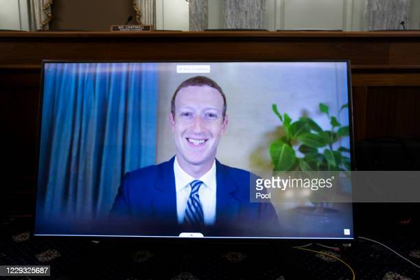 CEO of Facebook Mark Zuckerberg appears on a monitor as he testifies remotely during the Senate Commerce Science and Transportation Committee hearing...