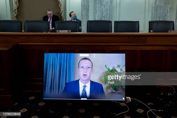 Of Facebook Mark Zuckerberg appears on a monitor as he testifies remotely during the Senate Commerce, Science, and Transportation Committee hearing...