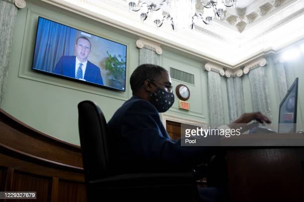 CEO of Facebook Mark Zuckerberg appears on a monitor behind a stenographer as he testifies remotely during the Senate Commerce Science and...