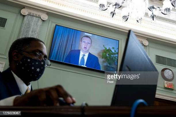 Of Facebook Mark Zuckerberg appears on a monitor behind a stenographer as he testifies remotely during the Senate Commerce, Science, and...