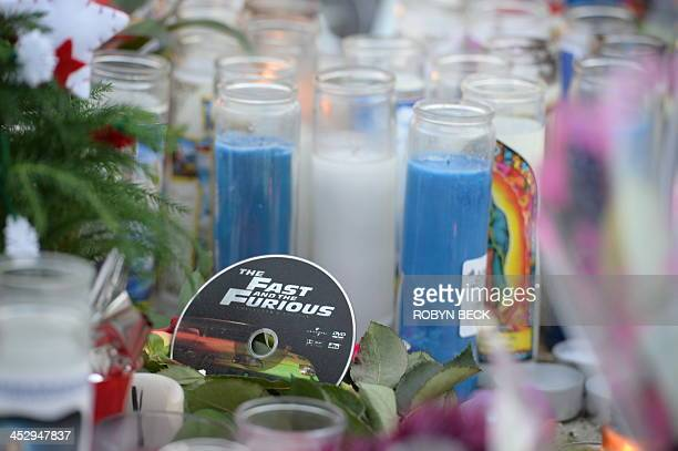 A DVD of Fast and Furious stands among flowers as fans pay their respects at the site of the car accident in which actor Paul Walker was killed in...