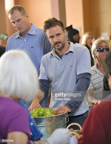 CEO of Feeding America and Master of Ceremonies Jay Bilas and Actor David Arquette pass out food to residents of the Tenderloin district at the...