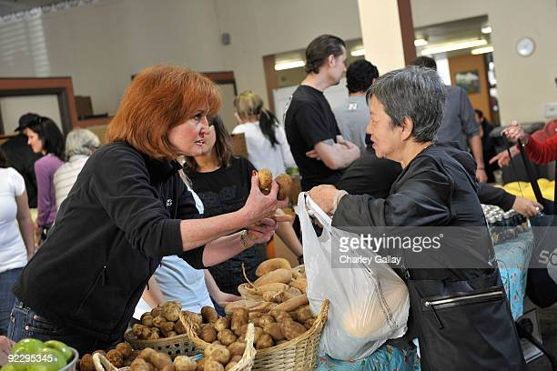 CEO of Feeding AmericaVicki Escarra passes out food to residents of the Tenderloin district at the Feeding America Food Bank on October 22 2009 in...