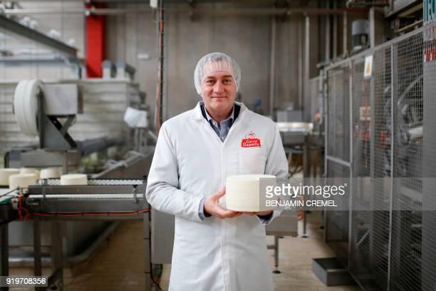 CEO of 'Garcia Baquero' cheese manufacturer Miguel Angel Garcia Baquero poses holding a Manchego cheese in the company's factory of Alcazar de San...