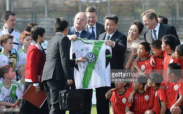 CEO of German carmaker Volkswagen Martin Winterkorn presenting to the Chinese President Xi Jingping and his wife Peng Liyuan a signed jersey of...