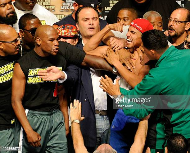 CEO of Golden Boy Promotions Richard Schaefer seperates boxers Floyd Mayweather Jr and Victor Ortiz during the weighin for their WBC welterweight...
