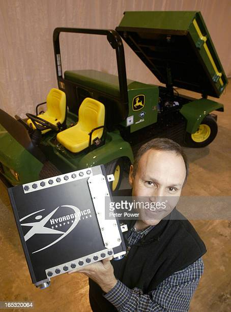 CEO of Hydrogenics Corporation Pierre Rivard holds a fuel cell stack while standing in front of a new John Deere technology demonstrator tractor that...