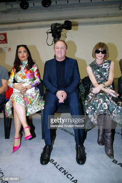 CEO of Kering Group FrancoisHenri Pinault sitting between his wife actress Salma Hayek and journalist Anna Wintour attend the Balenciaga show as part...