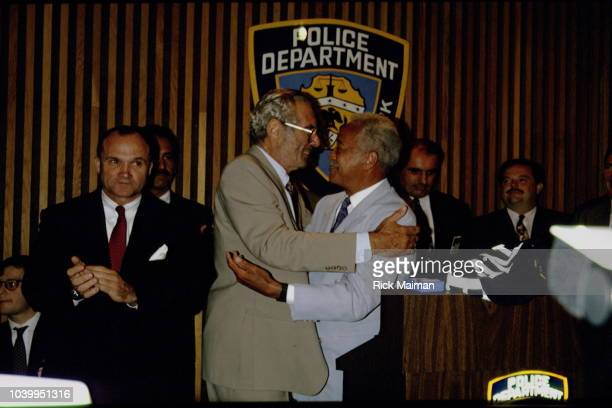 CEO of Lord West Formal Wear Harvey J Weinstein is congratulated by David Dinkins Mayor of New York City Commissioner of the New York City Police...