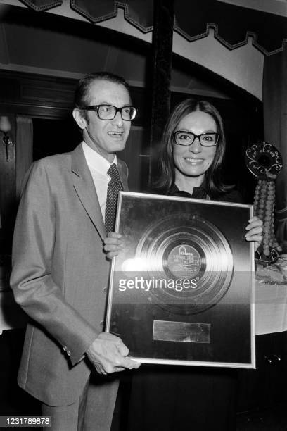 """Of Phonogram Louis Hazan poses with Greek singer Nana Mouskouri holding her """"Disque d'Or"""" she received on September 21, 1973 in Paris."""