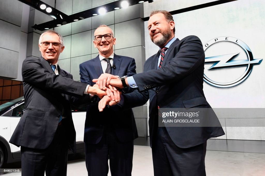 CEO of PSA Carlos Tavares, CEO of Opel group Karl-Thomas Neumann and General Motors President Dan Ammann shake hands in front of the new Opel Crossland X, during the 87th Geneva International Motor Show in Geneva, on March 7, 2017, a day after French carmaker PSA announced the acquisition of General Motors' European subsidiary, which includes the Opel and Vauxhall brands. Europe's biggest annual car show kicks off in Geneva with luxury and crossover vehicles under the limelight, but with the emissions scandal still hanging over the industry. /