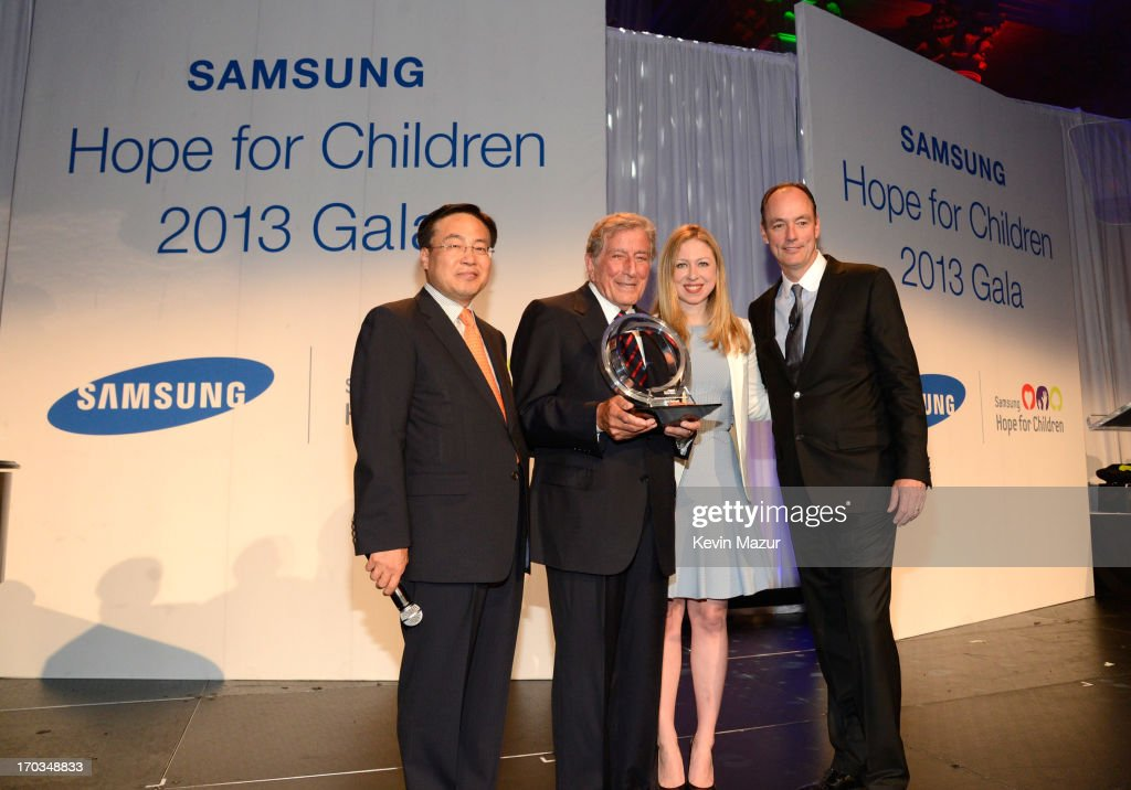 CEO of Samsung Electronics America YK Kim, Tony Bennett, Chelsea Clinton and President of Samsung Electronics America Tim Baxter on stage at the Samsung's Annual Hope for Children Gala at CiprianiÕs in Wall Street on June 11, 2013 in New York City.