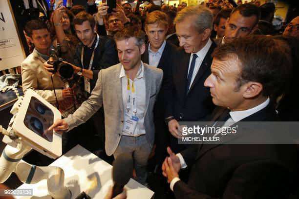 CEO of Spoonai Jerome Monceaux points to a screen as he talks to LVMH luxury group CEO Bernard Arnault and French President Emmanuel Macron as they...
