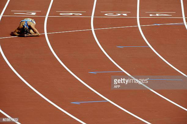 of the US Diana Pickler rests on the ground after the women's Heptathlon 100m Hurdles heat 5 at the National stadium as part of the 2008 Beijing...