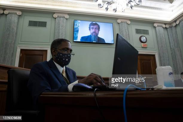 Of Twitter Jack Dorsey appears on a monitor behind a stenographer as he testifies remotely during the Senate Commerce, Science, and Transportation...