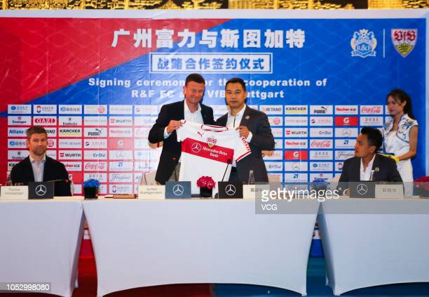 CMO of VfB Stuttgart Jochen Roettgermann and Vice Chairman of Guangzhou RF Huang Shenghua pose with jerseys during the signing ceremony for the...