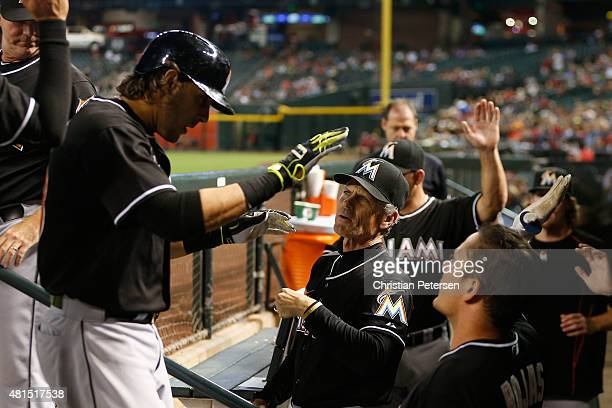 Of/base running/bunting coach Brett Butler of the Miami Marlins highfives Michael Morse after Morse hit a solo home run against the Arizona...