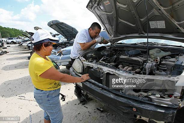 Ofelia Gutierrez, left, helps her husband Francisco Gutierrez, of Kissimmee, pull out a speed sensor from a 1994 Honda Accord to repair their car at...