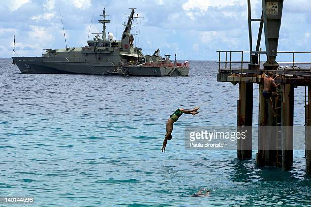 Off duty Australian Navy personnel enjoy some relaxation diving into the Indian ocean near by a Australian Navy boat docked at the Flying Fish Cove...